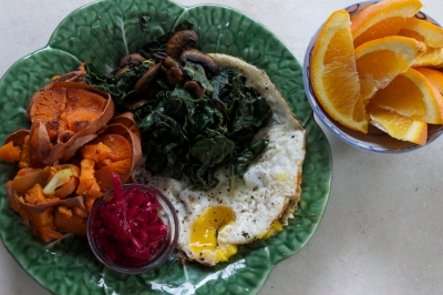 fried pastured eggs with sauteed mushrooms and leftover steamed kale, fried leftover sweet yam, sauerkraut, and orange
